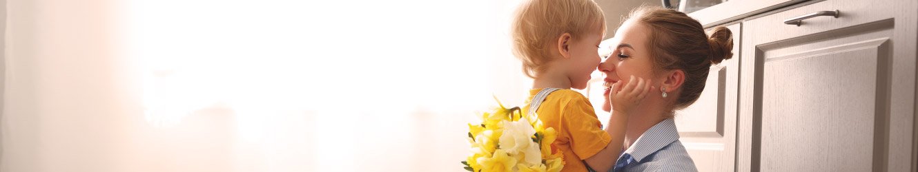 Young mother holds her son and a bouquet of flowers.