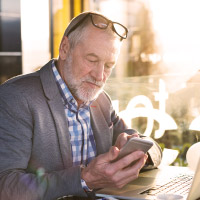 Mature businessman looks at his phone.