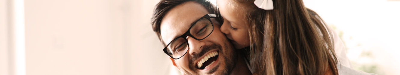 Father laughs as daughter carried on his back kisses his cheek.