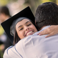 Graduating daughter embraces her father.